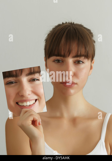 Young woman holding photograph of herself - Stock Image