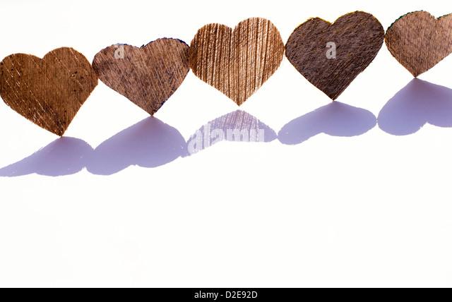 Line of coconut husk bark heart shapes with shadows on white - Stock-Bilder