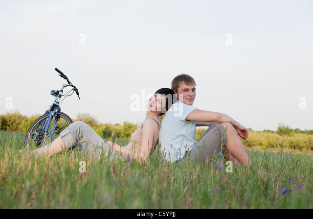 Russia, Voronezh, couple sitting in meadow - Stock Image
