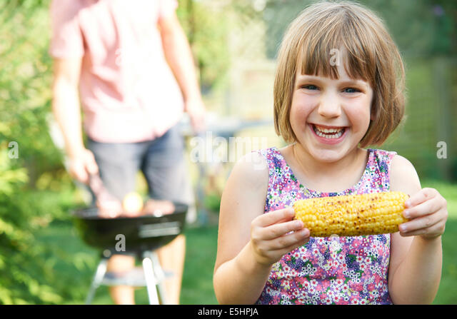 Young Girl Eating Sweetcorn At Family Barbeque - Stock-Bilder
