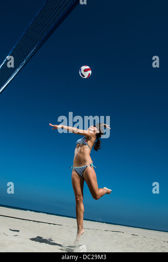 Female beach volleyball player hitting ball - Stock Image