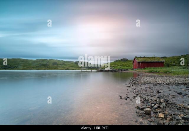 Pink lights of the midnight sun illuminate sea and the typical rorbu, Holdalsvatnet, Vestvagoy, Lofoten Islands, - Stock Image
