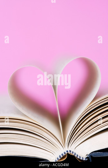 Heart shape made from book pages against a pink background - Stock-Bilder