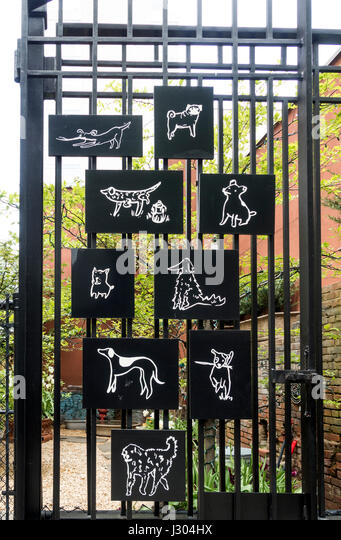 Charming black and white illustrations of dogs on the entrance gate of a Soho dog run in New York City - Stock-Bilder