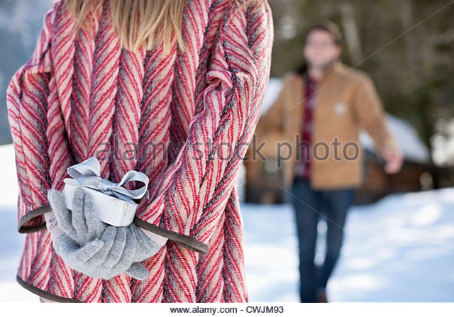 Man approaching woman with Christmas gift behind back - Stock Image