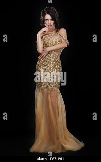 Formal Party. Glamorous Fashion Model in Elegant Golden Dress over Black - Stock Image
