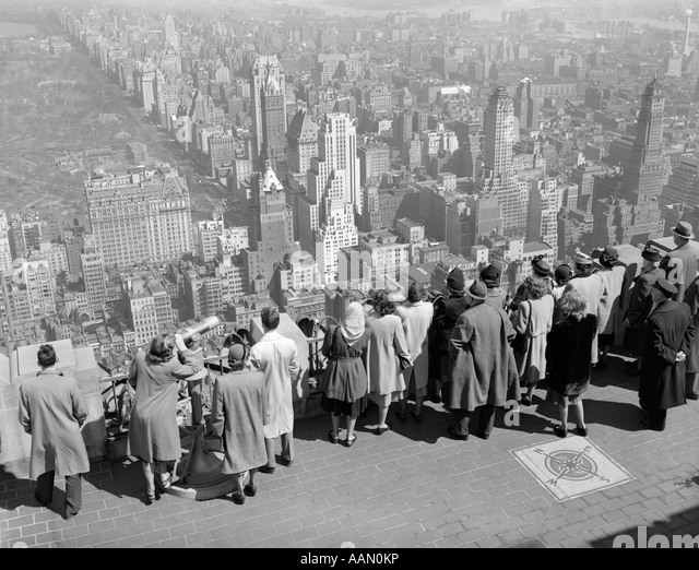 1940s GROUP OF TOURISTS STANDING ON TOP OF RCA BUILDING LOOKING OUT OVER CITY - Stock Image
