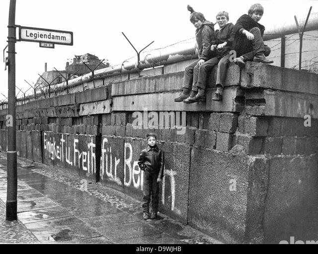 A group of children sits on the Berlin Wall at the 'Legiendamm' in the West Berlin borough Kreuzberg, March - Stock-Bilder