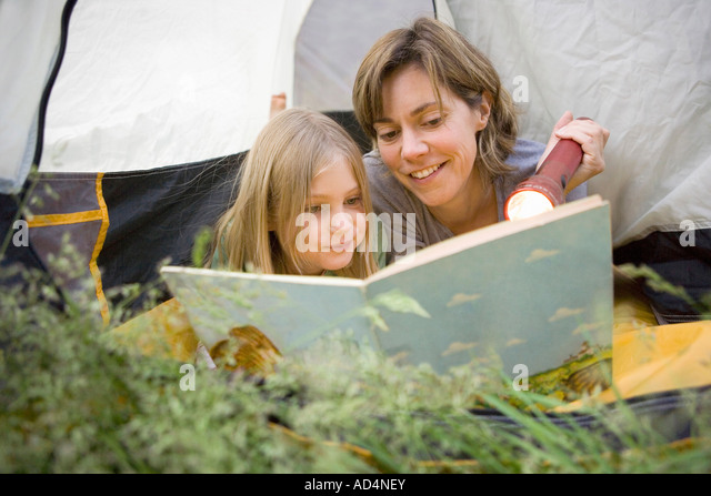 A mother and daughter peeking out of a tent and reading together - Stock-Bilder