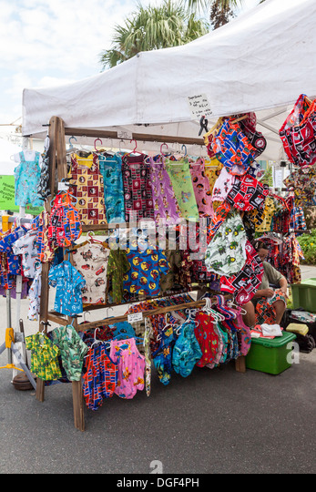 Colorful children's clothing on display in vendor's tent at arts and crafts festival. - Stock Image