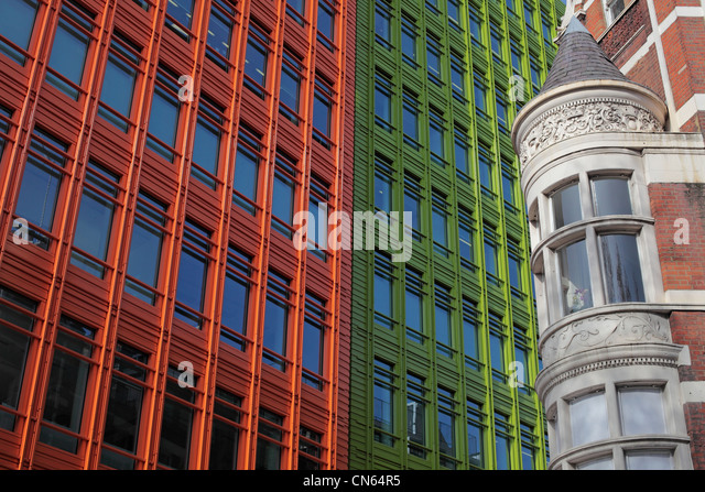 Old architecture next to a modern colourful building in London - Stock Image