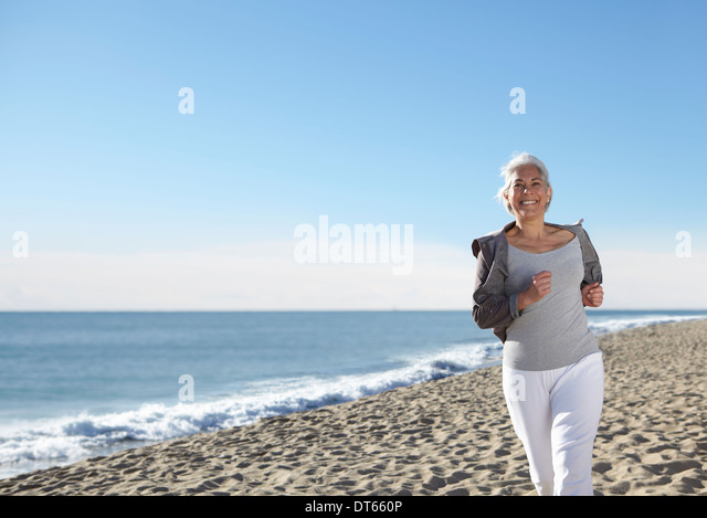 Mature woman jogging on beach - Stock Image
