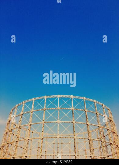 Skeleton structure of empty gasometer against a vivid blue sky with jet and contrail - Stock Image