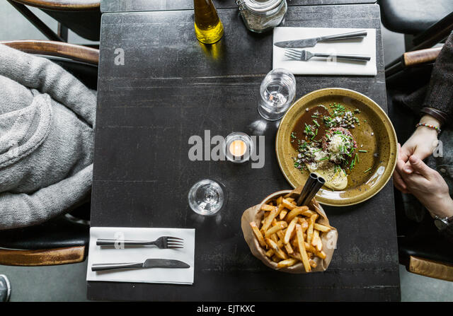 Cropped image of mother and son with food served on table - Stock-Bilder