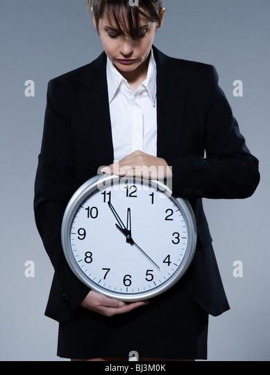beautiful woman on isolated backgound holding a clock - Stock Image