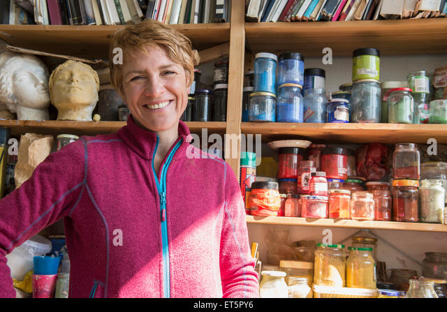 Female artist laughing against a shelf with colors and pigments, Bavaria, Germany - Stock Image