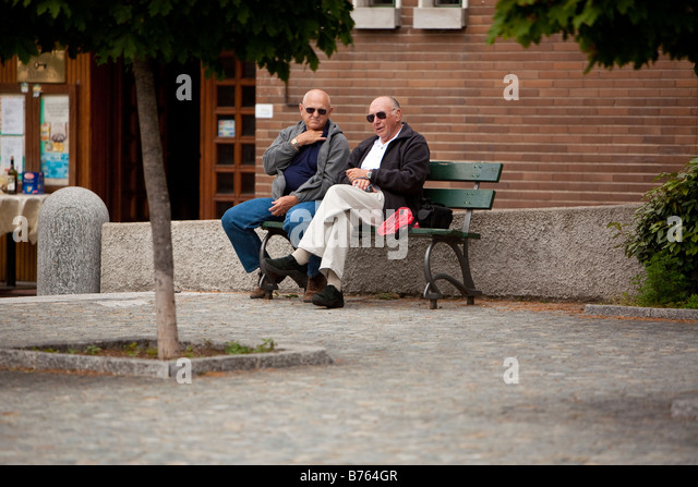 Two men sit on village bench in Brunate Italy - Stock Image