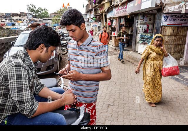 Mumbai India Asian Dharavi Shahu Nagar Road slum teen boy friends looking texting smartphone - Stock Image