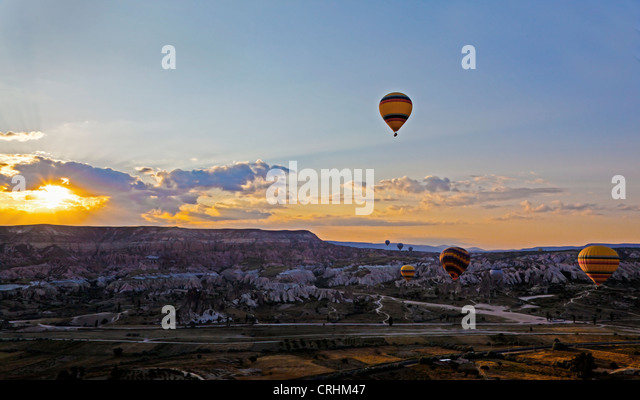 Dawn flight of hot air balloons over Cappadocia as the early morning sun peeks of the limestone hills onto the valley - Stock Image