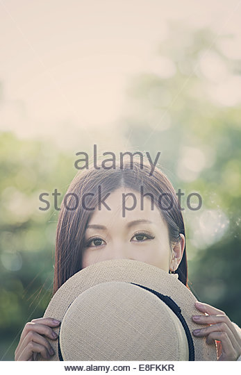 Portrait of girl holding hat - Stock Image