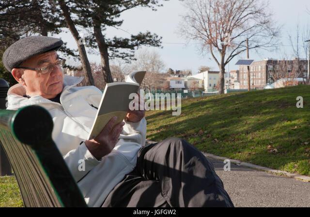 Hispanic man sitting on park bench reading book - Stock Image