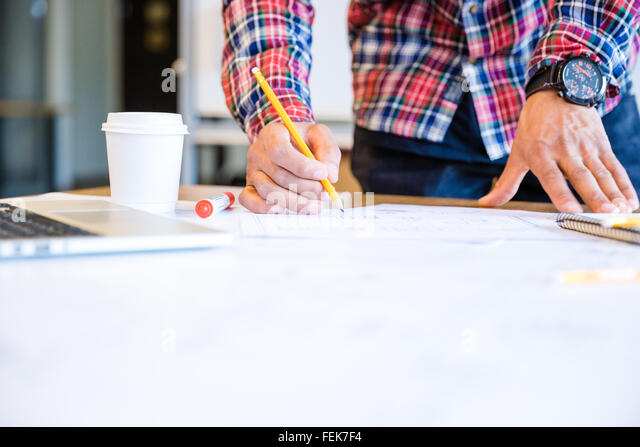 Young african american student drawing blueprint with pencil standing in classroom - Stock Image