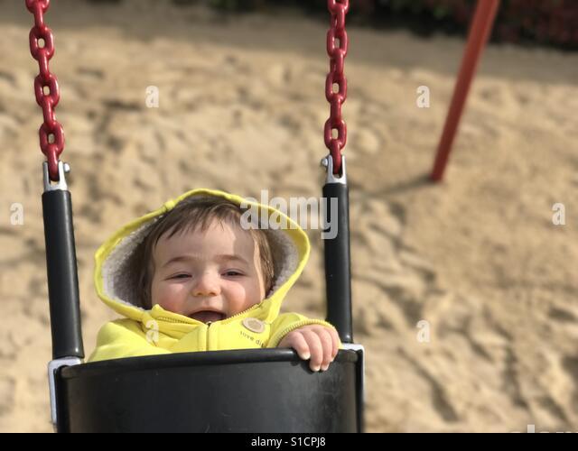 Baby swinging on the playground - Stock-Bilder