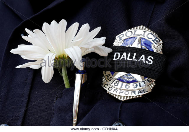A Dallas police officer wears a custom mourning band and a flower at a makeshift memorial at police headquarters - Stock-Bilder
