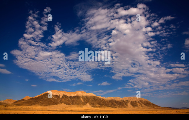 Clouds in blue sky over mountain, Namib Desert, Namibia, Africa - Stock Image