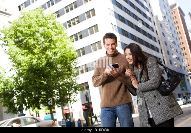 A young couple are strolling arm in arm through a downtown city area carrying a hand held device. - Stock Image