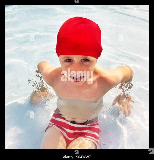 Five year old boy in a swimming pool wearing a bright red swimming cap - Stock Image
