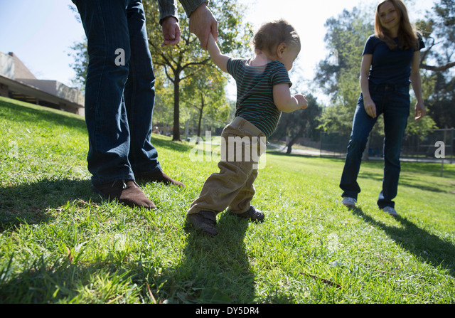 Baby boy learning to walk on grass - Stock Image