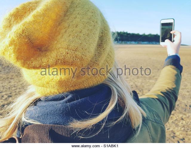 Pretty blonde with phone on beach. - Stock-Bilder