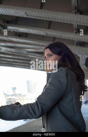 Attractive dark haired woman looks out from under a bridge in a tense and anxious urban setting - Stock Image