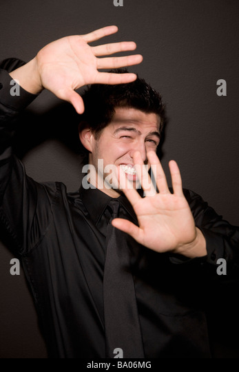 Man with hands blocking light - Stock Image