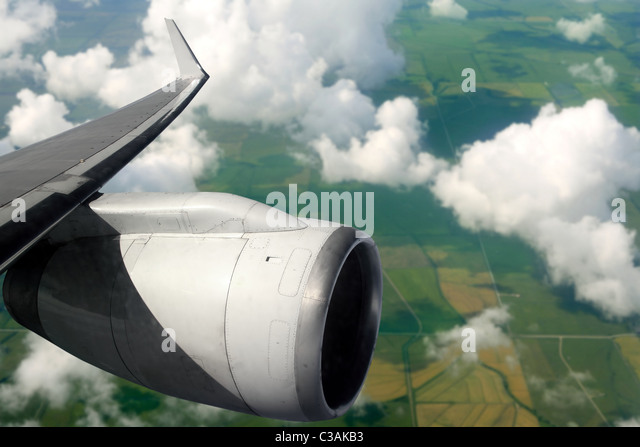 airplane wing aircraft turbine flying over agriculture fields - Stock Image