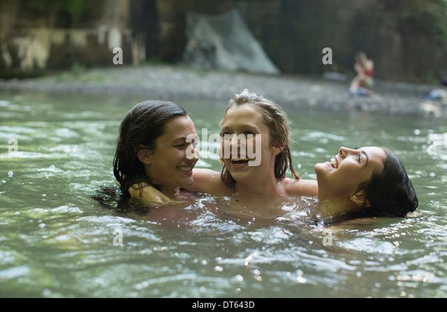 Teenage girls having fun in the river - Stock Image