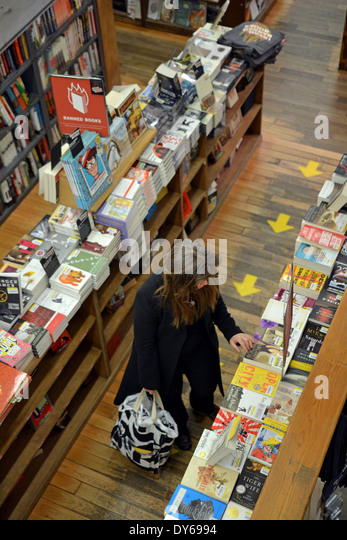 A woman shopping for books at the Strand Bookstore on Broadway in Greenwich Village, Manhattan, New York City. - Stock Image