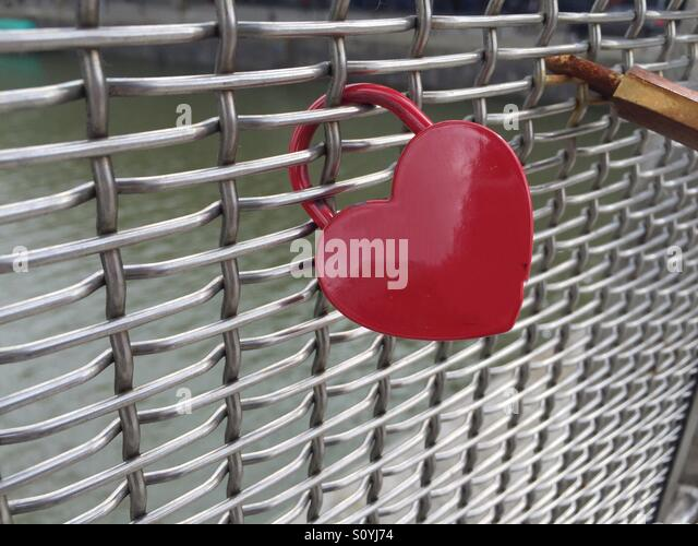 A red heart shaped padlock on a wire mesh. Seen on a footbridge in Bristol. Symbolic of love, marriage and relationships. - Stock Image