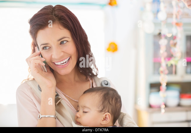 Mother with sleeping baby girl talking on cell phone - Stock Image