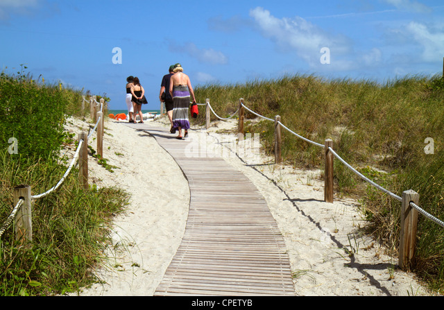 Miami Beach Florida dune walkway path sand grass sunbathers - Stock Image
