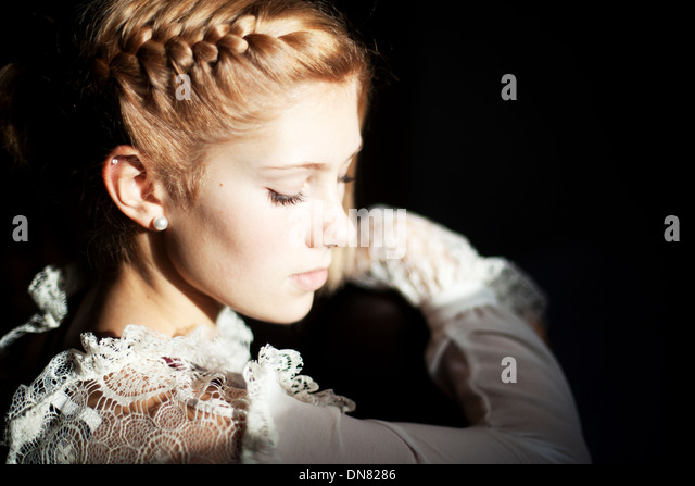 Portrait of a young woman, light and shadow - Stock Image