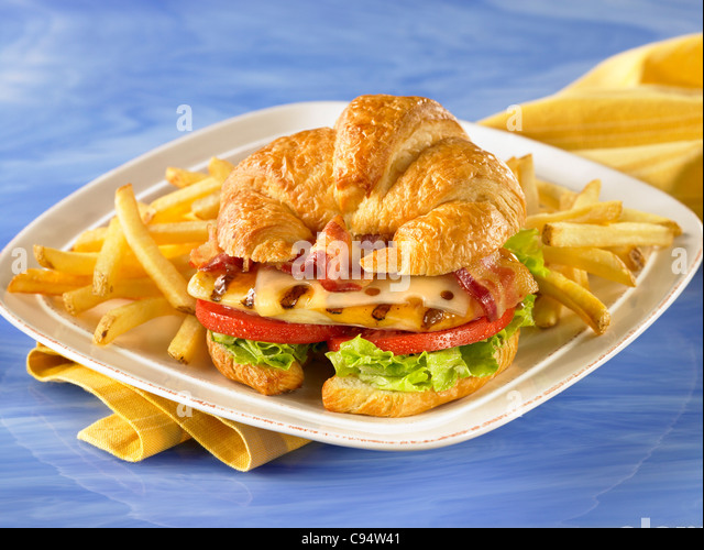 Gourmet croissant chicken sandwich with bacon, lettuce, tomato and swiss cheese served with french fries - Stock Image