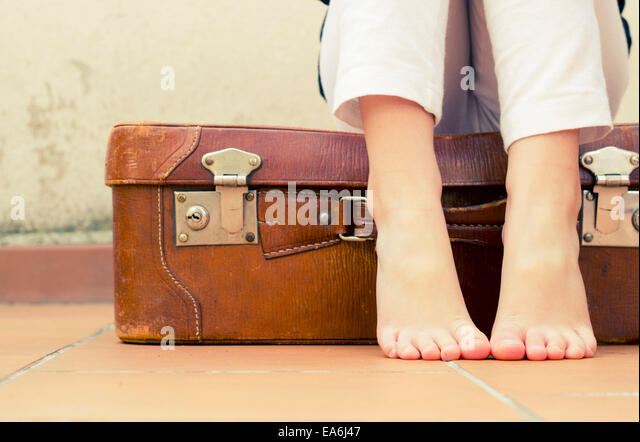 Girl ( 6-7 ) sitting on suitcase, low section - Stock Image