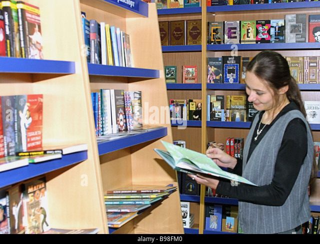 Girl chooses book at a store of Prosveshcheniye Education publishing house offering textbooks teaching aids maps - Stock Image