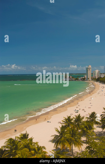 San Juan Puerto Rico Isla Verde beach with sunbathers, blue sky and resort hotels in background, palm trees lining - Stock Image