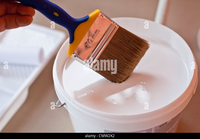 Person with paintbrush and paint - Stock Image