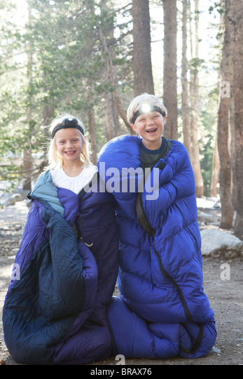 Boy and girl in sleeping bags - Stock Image