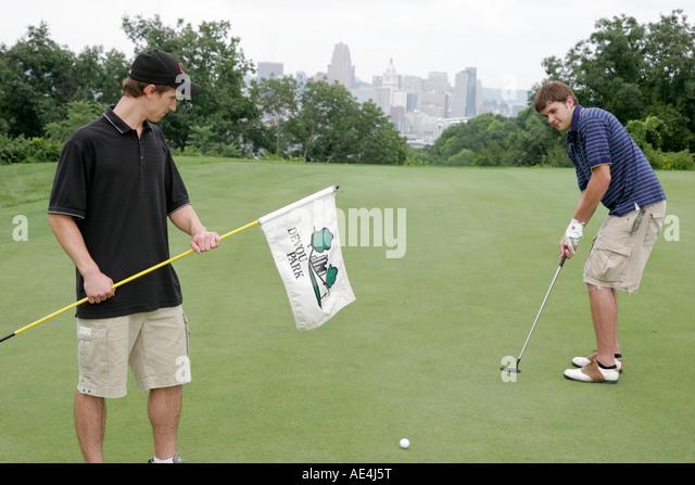 Kentucky Covington Devou Park Golf Course Cincinnati skyline men golfers green putting flag - Stock Image