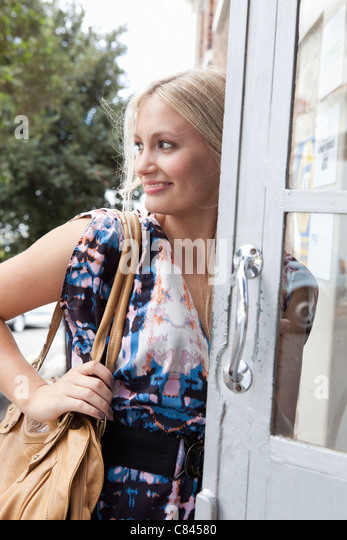Woman carrying large purse in doorway - Stock Image